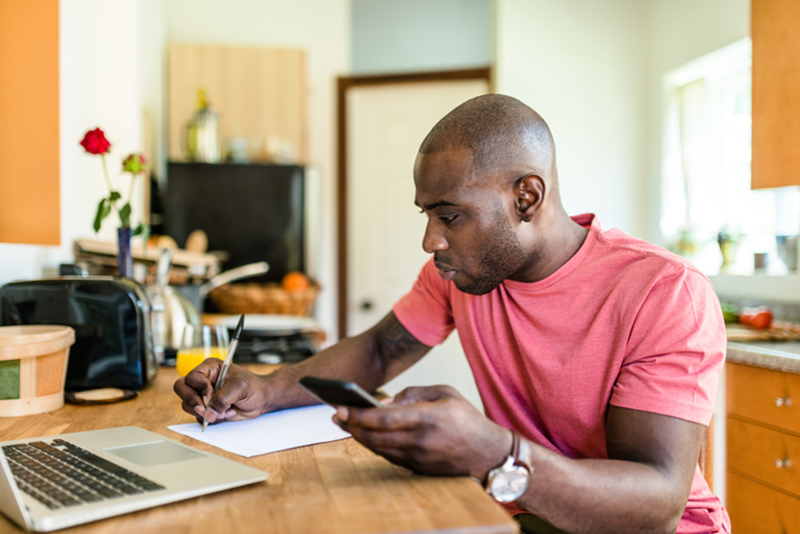 Man on his computer taking notes looking to start side hustles