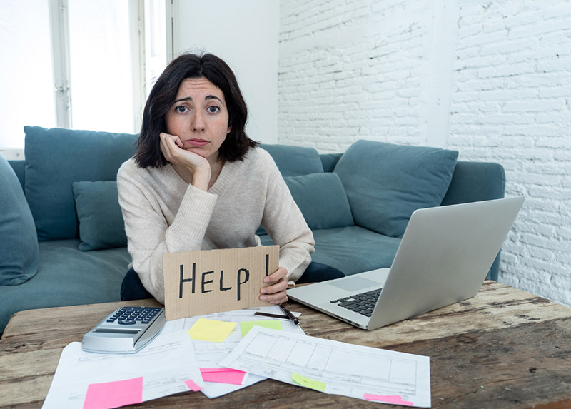 Woman holding up a help sign while looking at her finances, financial goals concept